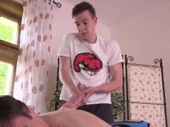Masseur tugging twink during massage