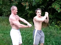 Dad bodybuilder and younger friend flex their muscles outdoor